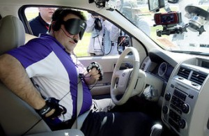 Blind driver Mark Riccobono makes adjustments to his equipment before driving a specially equipped car around the road course at Daytona International Speedway in Daytona Beach, Fla., Saturday, Jan. 29, 2011.