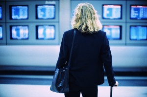 A woman with a cane looks at airport monitor screens