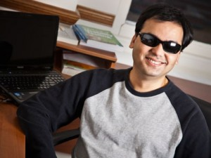 A man who is blind sits at his computer at home and smiles