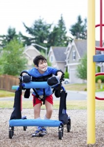 Boy in a walker at an accessible playground