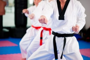 Taekwondo students in a gym. The master has a black belt. Others have a red belt.