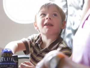 A boy eats potato chips on a JetBlue practice flight for kids with autism